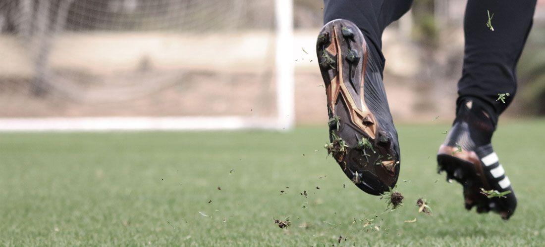 Imagen en primer plano de las piernas de un jugador de fútbol corriendo en un campo de césped natural