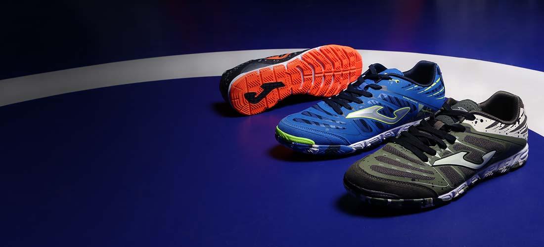 Tres zapatillas de fútbol sala Joma sobre pista azul