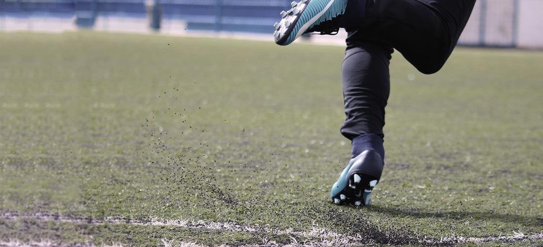 Imagen de las piernas de un jugador de fútbol corriendo en un campo de césped artificial